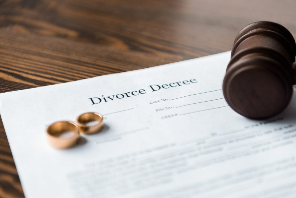 close-up view of divorce decree, wedding rings and wooden hammer